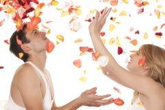 Man en de vrouw met bloemblaadjes van rozen Royalty-vrije Stock Foto