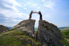 Man en een vrouw die, haar handen uitgestrekt aan elkaar, bij gespleten berg bevinden zich Stock Afbeelding