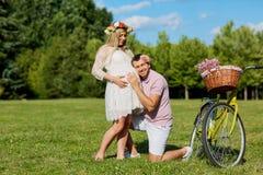 Man en een zwangere vrouwen gelukkige aard in park Jonge gelukkige famil Royalty-vrije Stock Fotografie