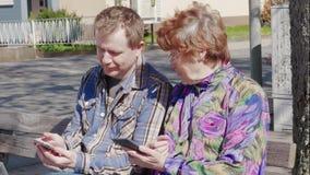 Man en hogere vrouwenzitting met mobiles openlucht, buren stock videobeelden