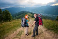 Man en roodharige vrouw op de weg in de bergen Royalty-vrije Stock Fotografie