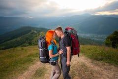 Man en roodharige vrouw op de weg in de bergen Stock Fotografie