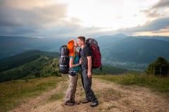 Man en roodharige vrouw op de weg in de bergen Royalty-vrije Stock Afbeelding