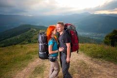 Man en roodharige vrouw op de weg in de bergen Stock Afbeeldingen