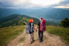 Man en roodharige vrouw op de weg in de bergen Royalty-vrije Stock Foto's