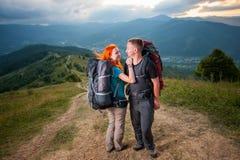 Man en roodharige vrouw op de weg in de bergen Stock Foto