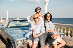 Man en twee mooie vrouwen die zich dichtbij uitstekende auto verenigen Stock Afbeelding
