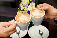 Man en van de vrouw handen en koffiekoppen Stock Foto