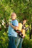 Man en vrouw bespoten bomen Stock Fotografie