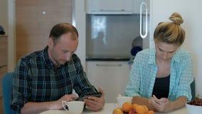 Man en vrouw bij de lijst stil belast met het bekijken van gadgets stock footage