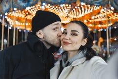Man en vrouw bij Kerstmis het eerlijke kussen en het maken Selfie Gelukkige verhoudingen stock foto