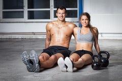 Man en vrouw - de zitting van het geschiktheidsteam op vloer met kettlebells royalty-vrije stock afbeeldingen