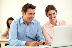 Man en vrouw die aan laptop werken stock afbeeldingen
