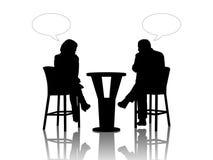 Man en vrouw die bij de lijst in een koffie spreken Stock Afbeelding