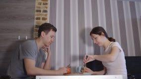 Man en vrouw die bij een lijst eten stock footage