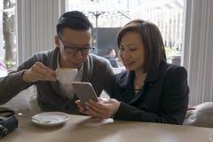 Man en vrouw die bij koffie telefoon bekijken Stock Foto