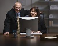 Man en Vrouw die in Bureau werken Stock Afbeeldingen