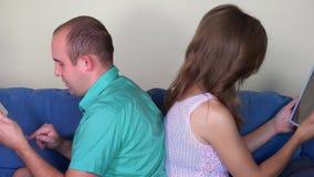Man en vrouw die de zitting van de tabletcomputer rijtjes op bank gebruiken close-up stock footage