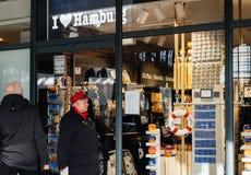 Man en vrouw die door herinneringswinkel overgaan in het station van Hamburg royalty-vrije stock foto's