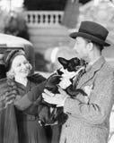 Man en vrouw die een kleine hond houden (Alle afgeschilderde personen leven niet langer en geen landgoed bestaat Leveranciersgara Royalty-vrije Stock Afbeeldingen