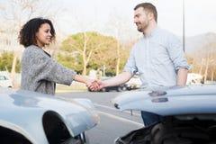 Man en vrouw die een overeenkomst na autoongeval bereiken royalty-vrije stock foto