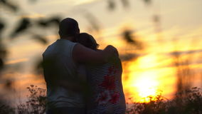 Man en vrouw die elkaar omhelzen die de zonsondergang bekijken stock video