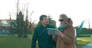 Man en vrouw die en tabletpc lopen met behulp van stock videobeelden
