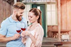 Man en vrouw die en wijn in wijnglazen omhelzen houden Stock Foto's