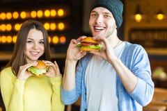 Man en vrouw die hamburger eten Het jonge meisje en de jonge mens houden burgers op handen royalty-vrije stock fotografie