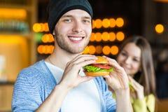 Man en vrouw die hamburger eten Het jonge meisje en de jonge mens houden burgers op handen royalty-vrije stock foto's