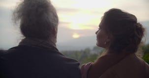 Man en vrouw die het ontspannen koesteren en in auto spreken die zonsondergang kijken Dicht geschoten achter Achter mening Kaukas stock video