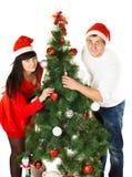 Man en vrouw die Kerstboom verfraaien Stock Foto