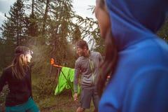 Man en vrouw die en met koplamp in avond dichtbij het kamperen gekscheren glimlachen Groep de reis van het de zomeravontuur van v Stock Fotografie