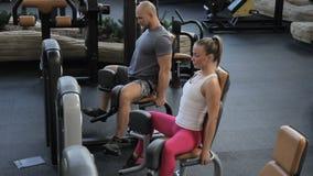 Man en vrouw die oefening in machine in gymnastiek doen stock videobeelden