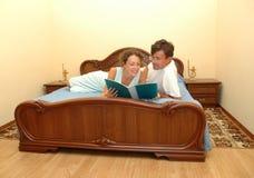 Man en vrouw die op bed wordt gelezen Royalty-vrije Stock Foto's