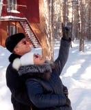 Man en vrouw die op de eekhoorns in de lange pijnbomen letten Stock Afbeelding