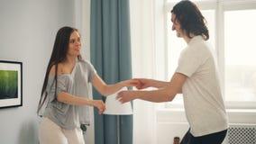Man en vrouw die samen op bed in moderne flat dansen die pret hebben stock videobeelden