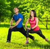 Man en vrouw die uitrekkende oefeningen doen stock foto's