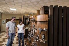 Man en vrouw die verschillende tapkranen in loodgieterswerkopslag bekijken royalty-vrije stock afbeeldingen