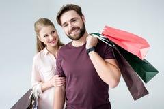 Man en vrouw die zich met het winkelen zakken bevinden en het glimlachen royalty-vrije stock fotografie