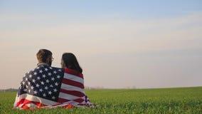 Man en vrouw door de vlag van Amerika wordt verpakt dat stock videobeelden