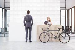 Man en vrouw en bicyclenear een ontvangstteller Stock Fotografie