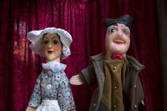 Man en vrouw guignols op rode gordijnen Royalty-vrije Stock Afbeeldingen