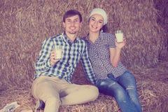Man en vrouw in hooi met melk stock fotografie
