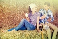Man en vrouw in hooi met melk royalty-vrije stock afbeeldingen