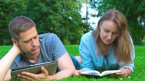 Man en vrouw lezen in het park stock videobeelden
