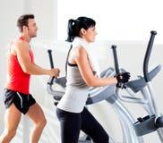Man en vrouw met elliptische dwarstrainer bij gymnastiek Royalty-vrije Stock Foto's