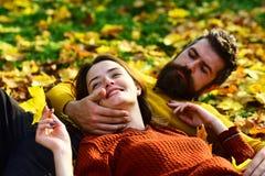 Man en vrouw met gelukkige gezichten op gras en bladeren Stock Afbeeldingen