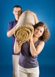 Man en vrouw met gerold tapijt Royalty-vrije Stock Afbeelding
