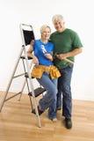 Man en vrouw met hulpmiddelen en ladder. royalty-vrije stock afbeeldingen